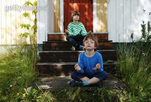 Two boys sitting cross legged on steps meditating - gettyimageskorea