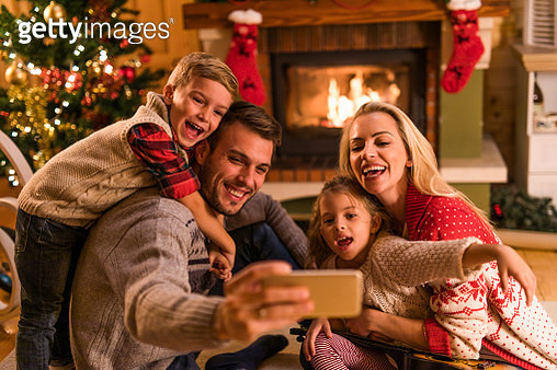 Happy family taking a selfie on Christmas Eve at home. - gettyimageskorea