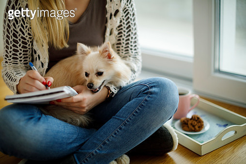 Young woman with dog sitting on the floor and writting notes - gettyimageskorea