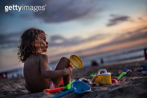 Happy little girl having fun in sand on the beach. It's beautiful sunset. - gettyimageskorea