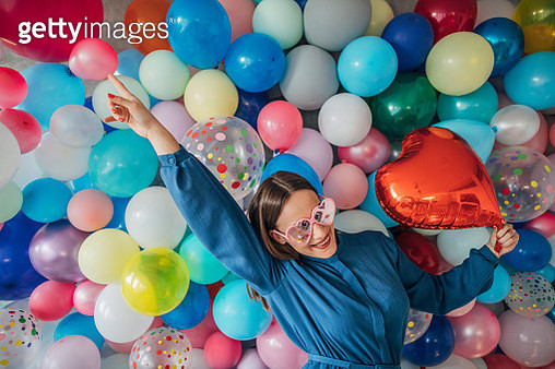 One woman, charming young lady standing in front of balloons, holding a heart shape balloon. - gettyimageskorea