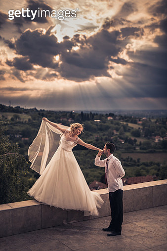 Romantic groom kissing a hand of his bride on a terrace. - gettyimageskorea