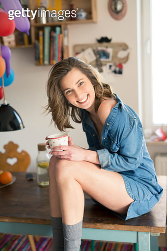 Portrait of laughing woman sitting on kitchen table with coffee mug - gettyimageskorea