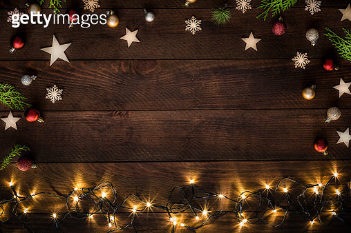 Top view of some wooden star and snowflake shapes, red, silver and gold christmas balls, pine twigs and christmas lights on a rustic wooden table. The Christmas lights are at the botton of the image and the other objects are disposed on a frame shape leav - gettyimageskorea