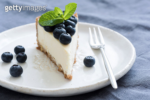 Slice Of Cheesecake With Fresh Blueberries And Mint Leaf On White Plate - gettyimageskorea