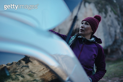 Woman taking backpack from her car trunk - gettyimageskorea