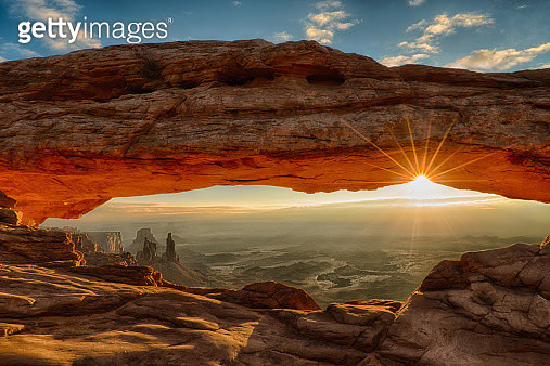 Sunburst under Mesa Arch, with the arches and landscape of Canyonlands National Park appearing under the arch - gettyimageskorea