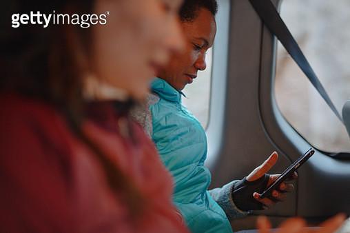 Women sitting in van using mobile phone - gettyimageskorea