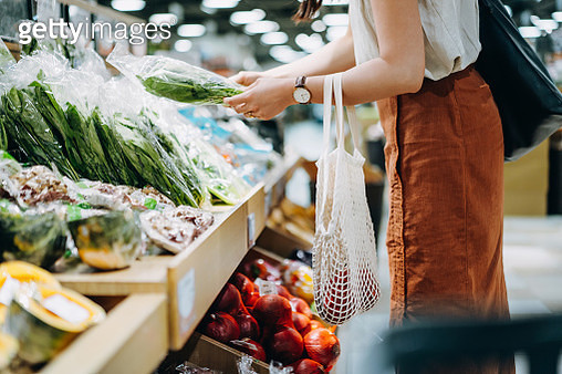 Cropped shot of young Asian woman shopping for fresh organic groceries in supermarket. She is shopping with a cotton mesh eco bag and carries a variety of fruits and vegetables. Zero waste concept - gettyimageskorea
