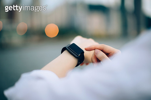 Close up of businesswoman checking her smartwatch in downtown city - gettyimageskorea