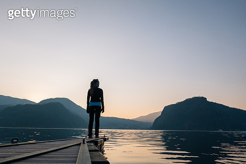Woman on the end of a walkway over a lake at sunrise - gettyimageskorea