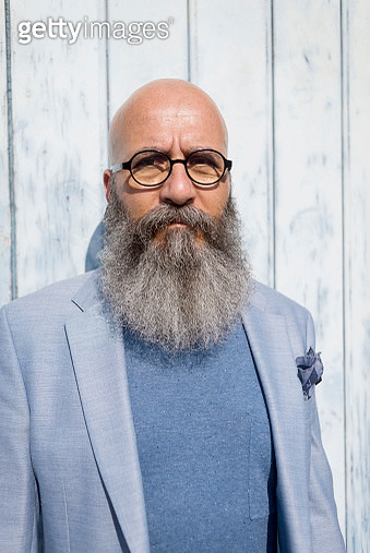 Portrait of hipster man with beard standing against wall during sunny day - gettyimageskorea
