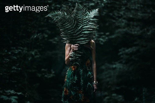 Woman Covering Face With Leaves While Standing In Forest - gettyimageskorea