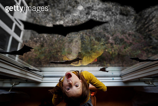 Overhead view of a girl standing by a window decorated with bat decorations for Halloween, United States - gettyimageskorea