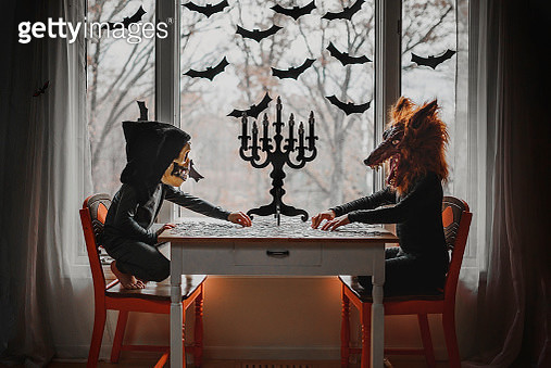 Two children in Halloween costumes sitting by a window doing a puzzle, United States - gettyimageskorea