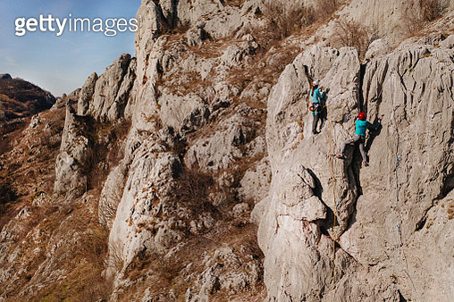 Two female rock climbers climbs up the cliff - gettyimageskorea
