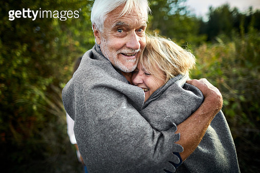 Portrait of happy mature couple wrapped in a blanket cuddling in the countryside - gettyimageskorea