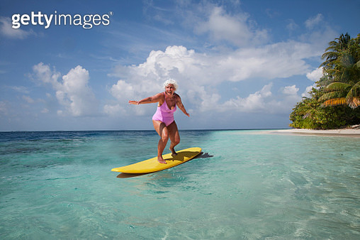 Indian Ocean. Maldives. A senior woman on a surf board in a turquoise water ocean - gettyimageskorea