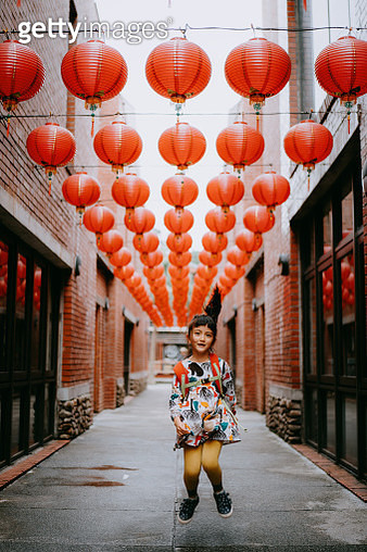Cute young mixed race girl jumping on street with red lanterns, Taiwan - gettyimageskorea