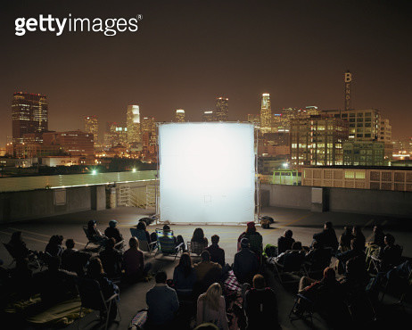 People on rooftop at night, sitting in front of projection screen - gettyimageskorea