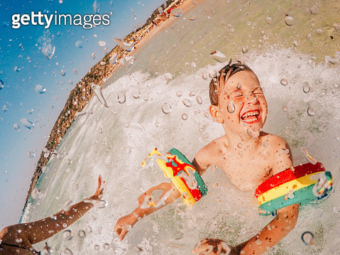 Photo is showing young boy, enjoying their fulfilled summer vacation by the ocean - gettyimageskorea