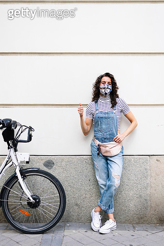 Mature woman wearing protective face mask showing thumbs up while standing by electric bicycle against wall - gettyimageskorea