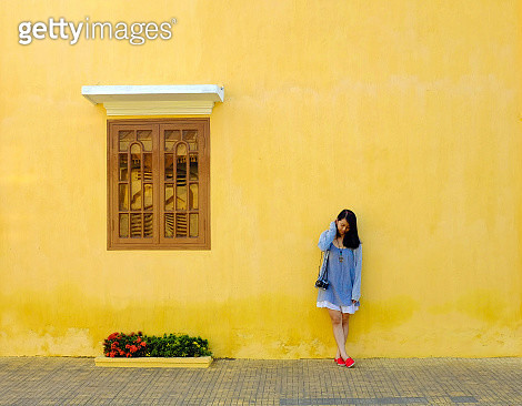 Full Length Of Woman Standing By Wall - gettyimageskorea