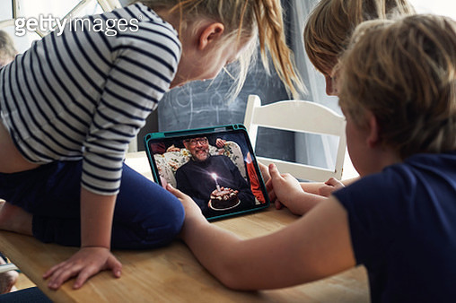 Family celebrating a birthday together on a video call - gettyimageskorea