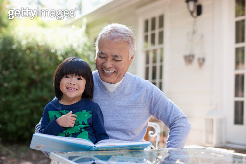 Older man and grandson reading together - gettyimageskorea