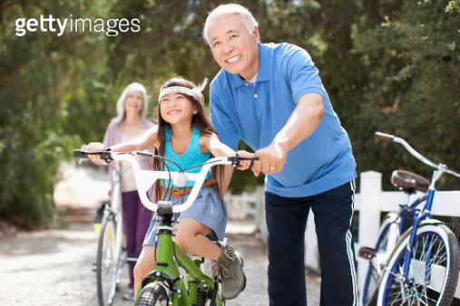 Older man helping granddaughter ride bicycle - gettyimageskorea