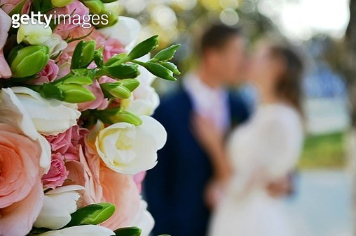 Close-Up Of Rose Bouquet With Couple In Background - gettyimageskorea