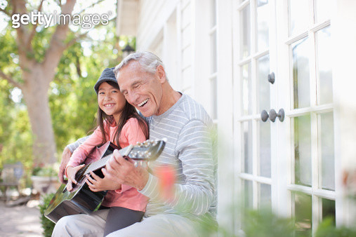 Older man and granddaughter playing guitar - gettyimageskorea