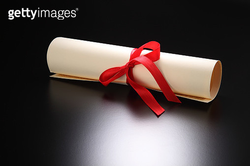 Close-Up Of Rolled Certificate Tied With Red Ribbon On Table - gettyimageskorea