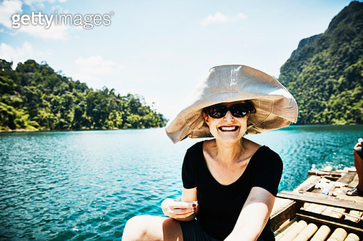 Smiling woman riding on bamboo raft in Khao Sok National Park Thailand - gettyimageskorea