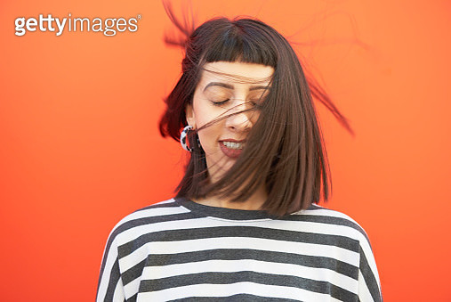 Portrait of woman with hair sweeping over face. - gettyimageskorea