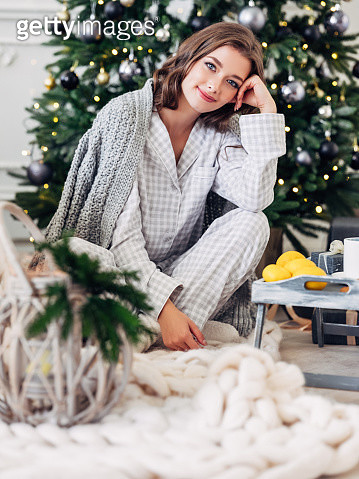 Beautiful girl sitting in a cozy atmosphere near the Christmas tree - gettyimageskorea