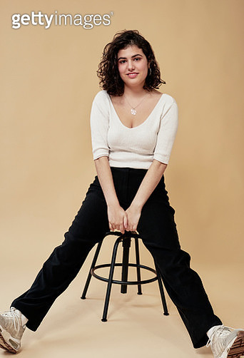 Smiling young woman sitting on a stool. - gettyimageskorea