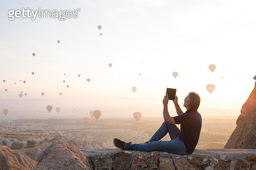 Man takes tablet pic of hot air balloons rising - gettyimageskorea