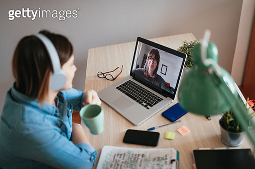 Woman teleconferencing with sister on laptop due to COVID-19 lockdown - gettyimageskorea