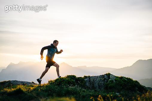 Young man runs on mountain ridge at sunrise - gettyimageskorea