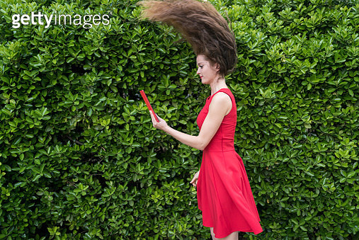 Lady in red amazed by something on her tablet - gettyimageskorea
