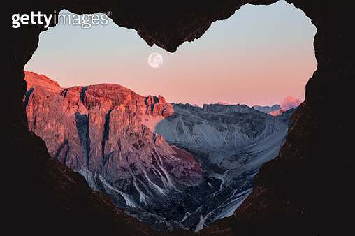 Composition of the Alps mountains during sunset with full moon from a cave with heart shape. - gettyimageskorea