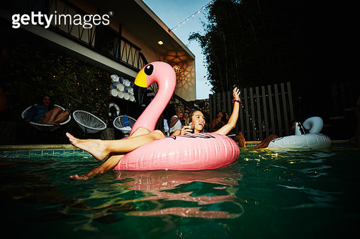 Woman relaxing in inflatable flamingo during hotel pool party - gettyimageskorea