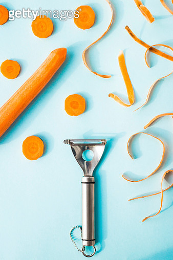 Close-Up Of Carrots And Peeler On Blue Background - gettyimageskorea