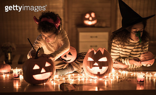 Two black siblings decorating Jack O' Lanterns on Halloween at home. - gettyimageskorea