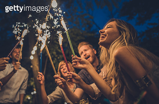 Large group of joyful friends having fun with flaming torches on a night party in the backyard. Focus is on woman in the foreground. - gettyimageskorea