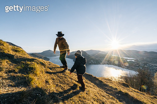 Father and young son explore a mountain path above a lake at sunrise - gettyimageskorea