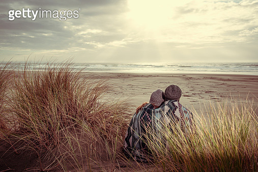 Couple Sitting on Sand Dunes at the Beach - gettyimageskorea