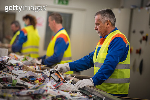 Workers sorting papers on factory assembly line for recycling at recycling plant. - gettyimageskorea