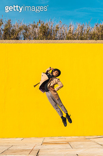 Young man dancing in front of yellow wall, jumping mid air - gettyimageskorea